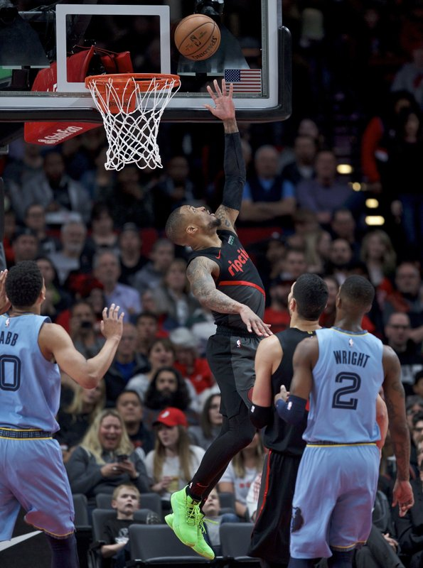 Portland Trail Blazers guard Damian Lillard, center, shoots between Memphis Grizzlies guard Delon Wright, right, and forward Ivan Rabb during the first half of an NBA basketball game in Portland, Ore. (AP Photo/Craig Mitchelldyer)