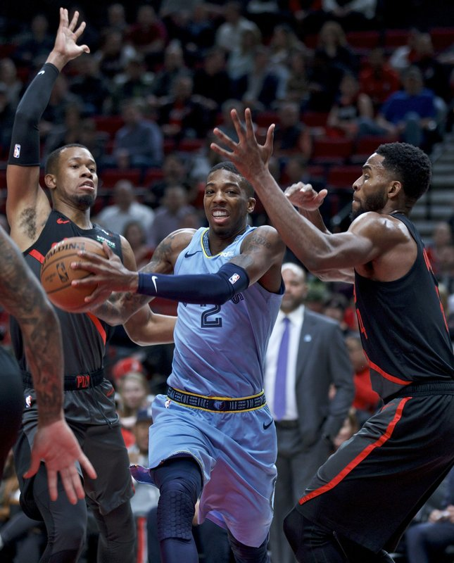 Memphis Grizzlies guard Delon Wright, center, drives to the basket past Portland Trail Blazers guard Rodney Hood, left, and forward Maurice Harkless, right, during the first half of an NBA basketball game in Portland, Ore. (AP Photo/Craig Mitchelldyer)