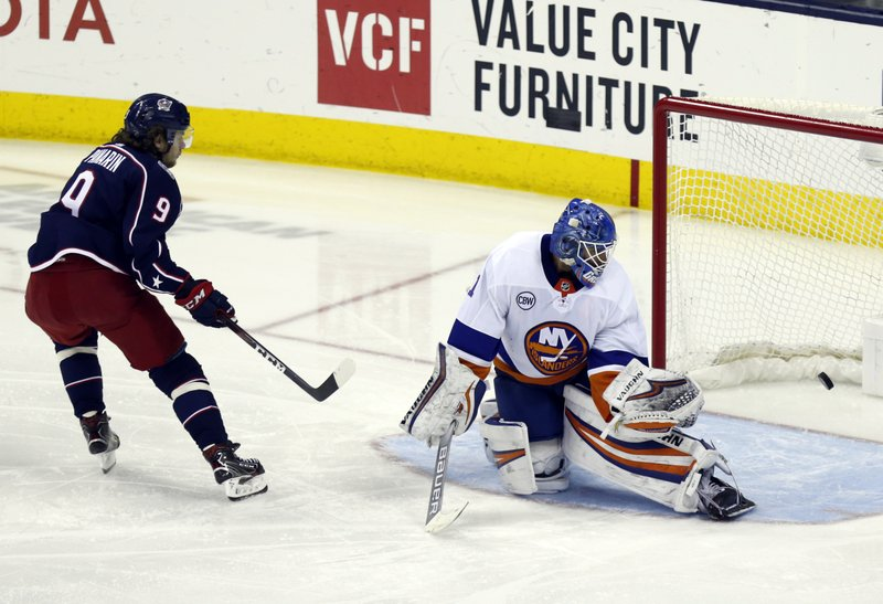Columbus Blue Jackets forward Artemi Panarin, left, of Russia, scores past New York Islanders goalie Thomas Greiss, of Germany, during the third period of an NHL hockey game in Columbus, Ohio, Tuesday, March 26, 2019. (AP Photo/Paul Vernon)