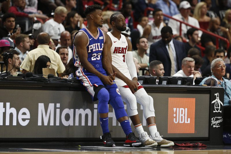 Miami Heat guard Dwyane Wade (3) and Philadelphia 76ers guard Jimmy Butler (23) wait to play in the first half of an NBA basketball game on Tuesday, April 9, 2019, in Miami. (AP Photo/Brynn Anderson)