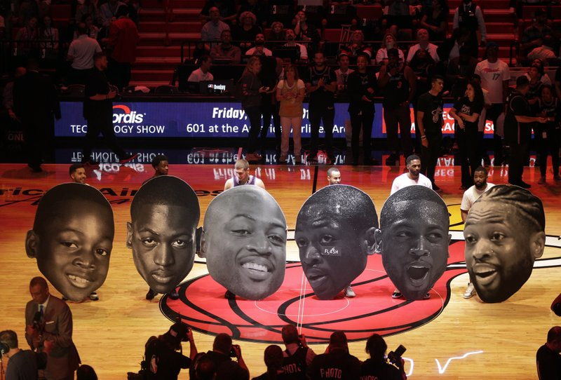 Cutout heads chronicling the career of Miami Heat guard Dwyane Wade sit on the court during a ceremony to honor Wade who is playing his final home regular season game when the Heat host the Philadelphia 76ers, Tuesday, April 9, 2019, in Miami. (AP Photo/Lynne Sladky)