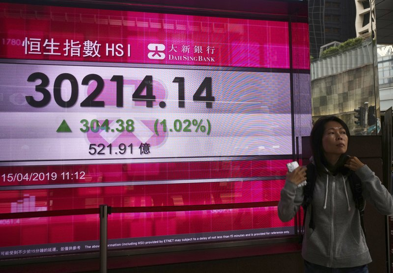A woman walks past an electronic board showing Hong Kong share index outside a local bank in Hong Kong, Monday, April 15, 2019. (AP Photo/Vincent Yu)