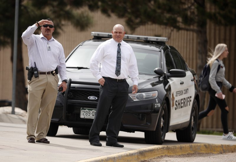 Columbine High School principal Scott Christy, right, joins an officer in watching as students leave the school late Tuesday, April 16, 2019, in Littleton, Colo. (AP Photo/David Zalubowski)