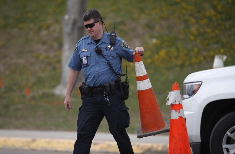 A Jefferson County, Colo. Schools officer blocks a driveway with a pylon outside Columbine High School as students leave late Tuesday, April 16, 2019, in Littleton, Colo. (AP Photo/David Zalubowski)