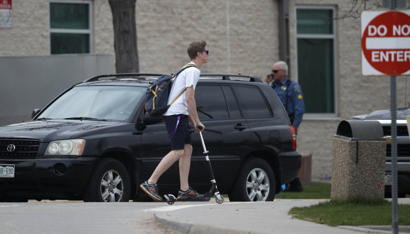 A student leaves by a scooter as parents wait in their vehicles for their children outside Columbine High School late Tuesday, April 16, 2019, in Littleton, Colo. (AP Photo/David Zalubowski)