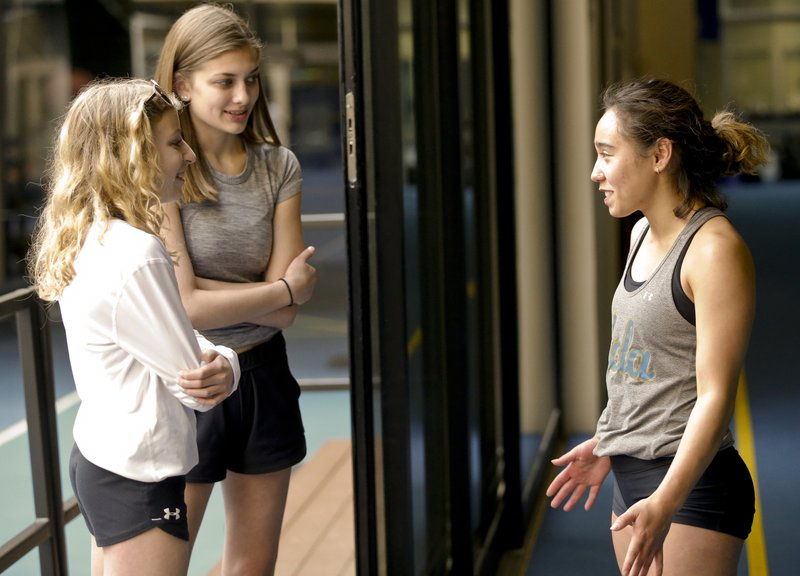 In this Thursday, April 11, 2019, photo, Gymnast Katelyn Ohashi, right, greets gymnasts and fans, Catelyn Zack, 15, left, and Greta Haroldson, 15, both visiting from St. (AP Photo/Damian Dovarganes)