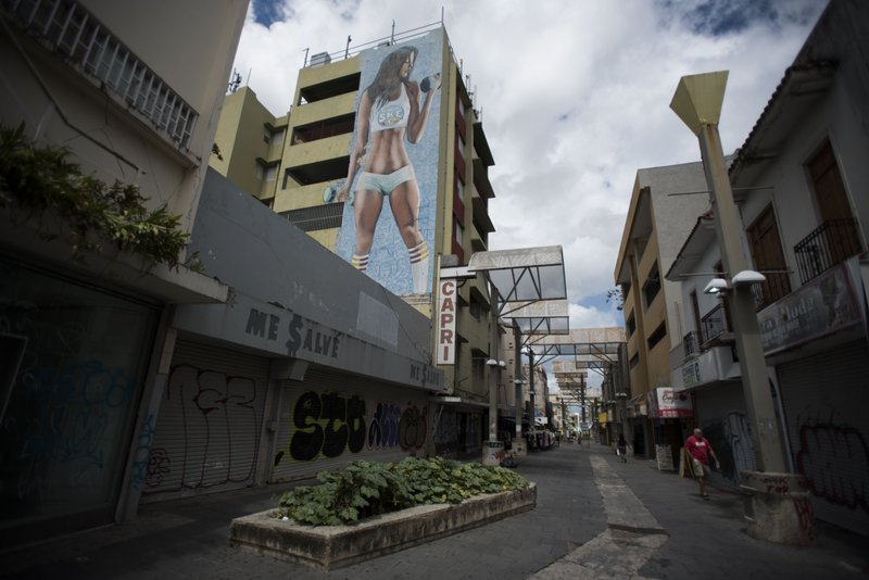 Shops are shuttered in the Paseo de Diego in San Juan, Puerto Rico, Wednesday, April 17, 2019. This central thoroughfare in Rio Piedras was filled years ago with stores that are closed and empty today. (AP Photo/Carlos Giusti)