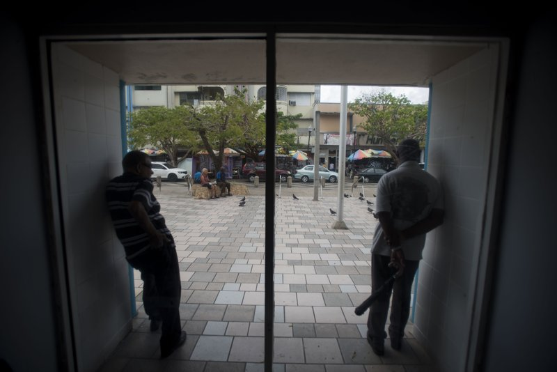 Residents stand inside the Plaza del Mercado in the Rio Piedras area of San Juan, Puerto Rico, Wednesday, April 17, 2019. (AP Photo/Carlos Giusti)