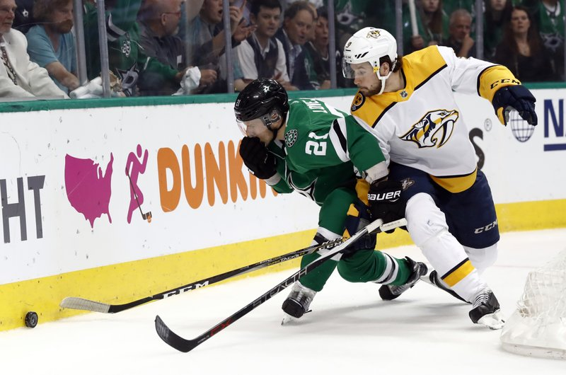 Dallas Stars defenseman Ben Lovejoy (21) holds his jaw after taking a stick to the face while competing for control of the puck against Nashville Predators' Filip Forsberg (9) in the second period of Game 6 in an NHL hockey first-round playoff series in Dallas, Monday, April 22, 2019. (AP Photo/Tony Gutierrez)