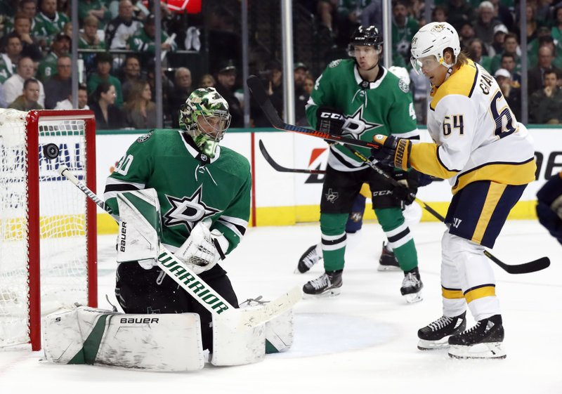 Dallas Stars goaltender Ben Bishop (30) and Nashville Predators center Mikael Granlund (64) watch as a Predators shot goes wide of the net in the second period of Game 6 in an NHL hockey first-round playoff series in Dallas, Monday, April 22, 2019. (AP Photo/Tony Gutierrez)