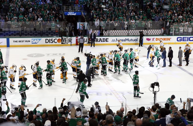 The Nashville Predators and Dallas Stars line up to congratulate each other after the Stars' 2-1 overtime win in Game 6 of an NHL hockey first-round playoff series in Dallas, Monday, April 22, 2019. (AP Photo/Tony Gutierrez)