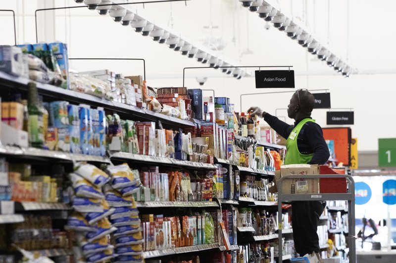 A Walmart associate arranges items on a shelf at a Walmart Neighborhood Market, Wednesday, April 24, 2019, in Levittown, N. (AP Photo/Mark Lennihan)
