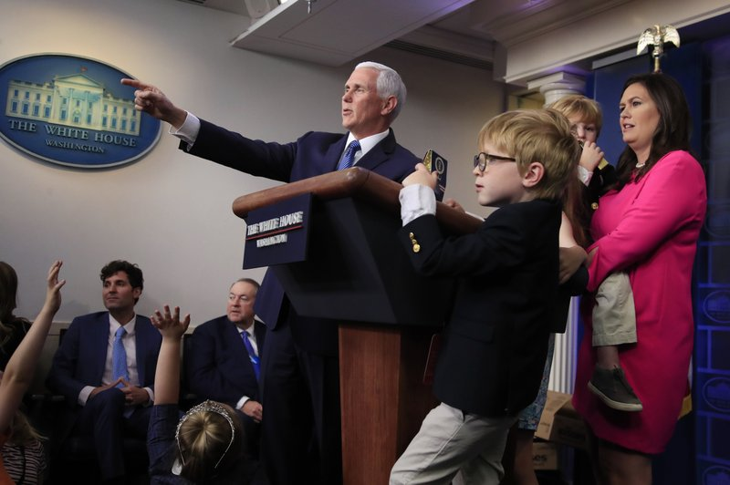 Vice President Mike Pence makes a surprise appearance as White House press secretary Sarah Huckabee Sanders holding her children, conducts a briefing for children of journalists and White House staff in the Brady press briefing room at the White House in Washington, Thursday, April 25, 2019, to commemorate Take Our Daughters and Sons to Work Day. (AP Photo/Manuel Balce Ceneta)