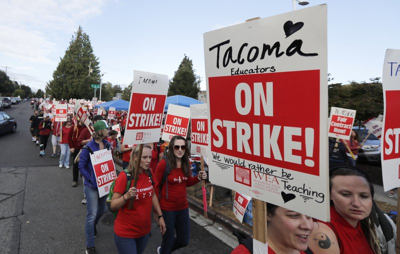 FILE - In this Monday, Sept. 10, 2018 file photo, striking teachers carry picket signs as they march around the Tacoma School District Central Administration Building, in Tacoma, Wash. (AP Photo/Ted S. Warren,File)