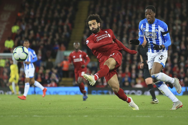 Liverpool's Mohamed Salah shoots on goal during the English Premier League soccer match between Liverpool and Huddersfield Town at Anfield Stadium, in Liverpool, England, Friday, April 26, 2019.(AP Photo/Jon Super)