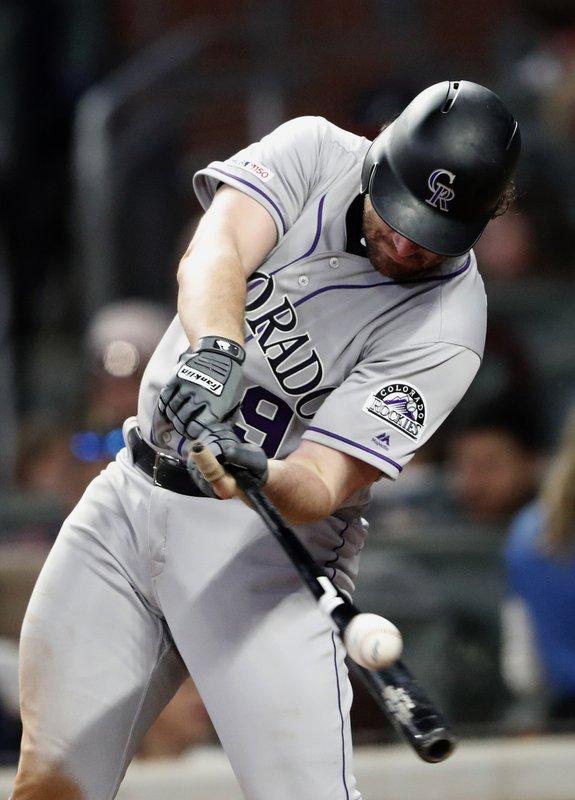 Colorado Rockies' Daniel Murphy (9) connects on an RBI-double in the sixth inning of a baseball game against the Atlanta Braves, Friday, April 26, 2019, in Atlanta.(AP Photo/John Bazemore)