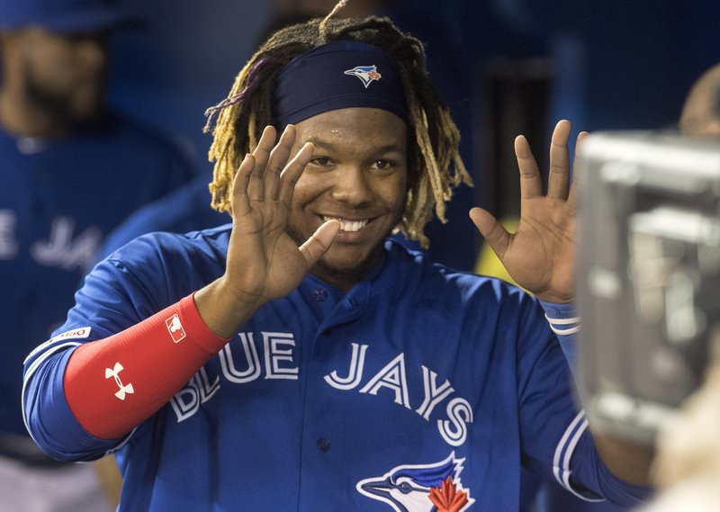 Toronto Blue Jays' Vladimir Guerrero Jr. smiles for a television camera looking into the dugout in the sixth inning of a baseball game against the Oakland Athletics in Toronto, Saturday April 27, 2019. (Fred Thornhill/The Canadian Press via AP)
