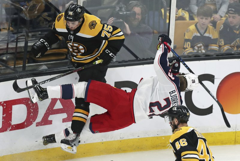 Columbus Blue Jackets right wing Oliver Bjorkstrand (28) is upended by Boston Bruins defenseman Connor Clifton (75) while chasing the puck during the first period of Game 2 of an NHL hockey second-round playoff series, Saturday, April 27, 2019, in Boston. (AP Photo/Charles Krupa)