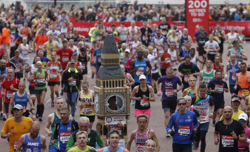 Lukas Bates wearing a costume of the Queen Elizabeth Tower (known as Big Ben) runs with the crowd towards the finish line of the 39th London Marathon in London, Sunday, April 28, 2019. (AP Photo/Alastair Grant)