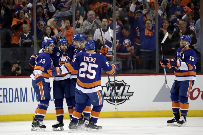 New York Islanders players celebrate a power-play goal by Mathew Barzal, far left, during the first period of Game 2 of an NHL hockey second-round playoff series against the Carolina Hurricanes, Sunday, April 28, 2019, in New York. (AP Photo/Julio Cortez)