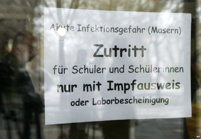 FILE - A sign at the entrance of a school in Freiburg, southern Germany, Apri