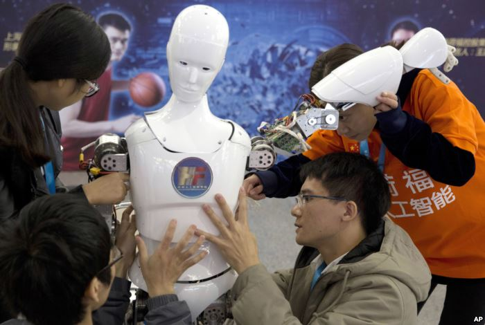 FILE - Chinese students work on the Ares, a humanoid bipedal robot, displayed