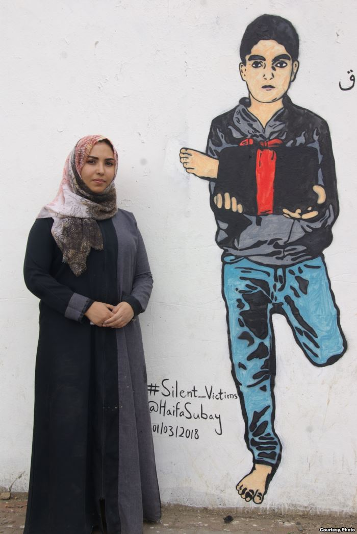 Yemeni artist Haifa Subay stands in front of one of her murals in the Yemeni