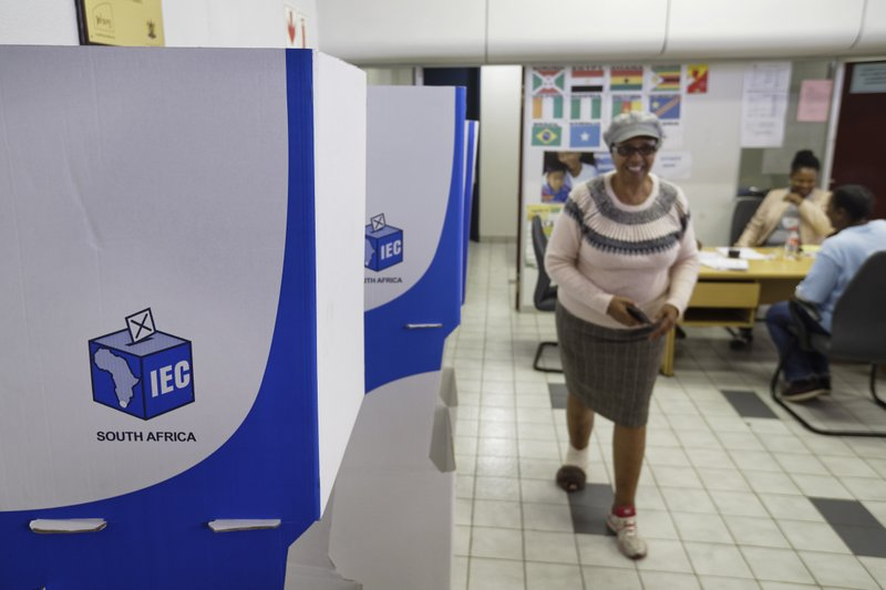 An electoral worker walks past polling booths readied ahead of Wednesday's election, at a polling station in downtown Johannesburg, South Africa Tuesday, May 7, 2019. (AP Photo/Ben Curtis)