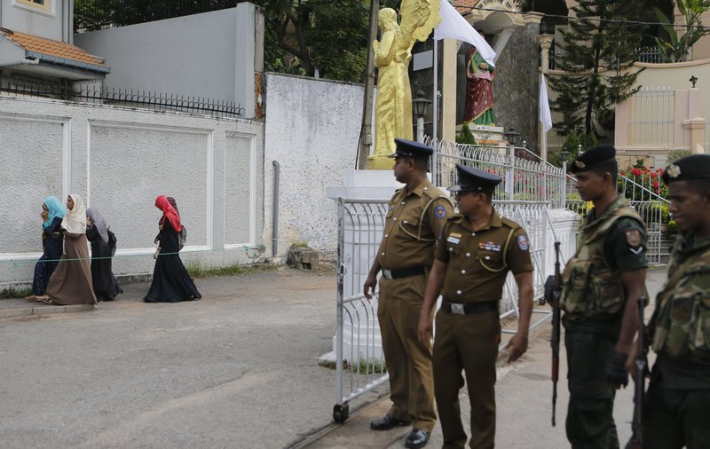 In this Sunday, May 12, 2019, photo, Sri Lankan soldiers watch as a group of Muslim students walk past a closed catholic convent in Colombo, Sri Lanka. (AP Photo/Eranga Jayawardena)