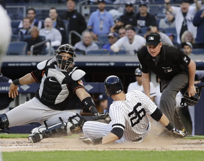 New York Yankees' DJ LeMahieu, right, slides past Baltimore Orioles catcher Pedro Severino, left, to score on a Luke Voit double during the third inning in the second baseball game of a doubleheader Wednesday, May 15, 2019, in New York. (AP Photo/Frank Franklin II)