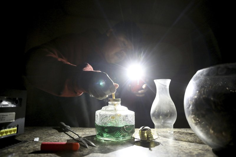 In this Wednesday, May 8, 2019 photo, Jimmie Long Jr. uses his cell phone flashlight to repair an oil lamp inside his Kaibwto home on the Navajo Reservation. Long and his wife, Miranda Haskie, were spending one last night without electricity in their home before being connected to the grid on Thursday, May 16, 2019. An ambitious project to connect homes to the electric grid on the country's largest American Indian reservation is wrapping up. Utility crews from across the U.S. have volunteered their time over the past few weeks to hook up about 300 homes on the Navajo Nation. (AP Photo/Jake Bacon)