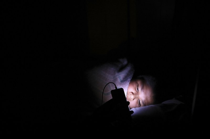 In this Wednesday, May 8, 2019 photo, Jayden Long, 13, watches Netflix on his cell phone shortly after sunset. Jayden's family has spent most of his life living in a home without electricity. An ambitious project to connect homes to the electric grid on the country's largest American Indian reservation is wrapping up. Utility crews from across the U.S. have volunteered their time over the past few weeks to hook up about 300 homes on the Navajo Nation. (AP Photo/Jake Bacon)