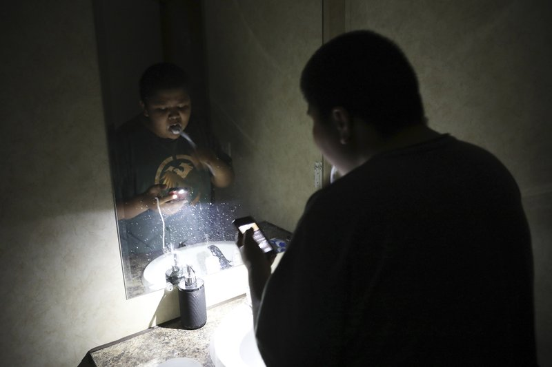 In this Wednesday, May 8, 2019 photo, Jayden Long, 13, brushes his teeth by cell phone light in the bathroom of his home on the Navajo Reservation. Long has spent more than a decade living with his family in a home with no electricity relying on a generator for power. An ambitious project to connect homes to the electric grid on the country's largest American Indian reservation is wrapping up Utility crews from across the U.S. have volunteered their time over the past few weeks to hook up about 300 homes on the Navajo Nation. (AP Photo/Jake Bacon)
