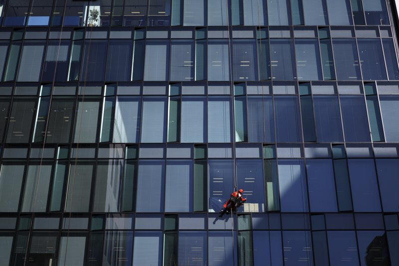 In this Jan. 10, 2018 photo, a worker cleans windows of an office building in Tokyo. The Japanese government says the economy grew at an annual pace of 2.1% in the first quarter, marking the second straight quarter of expansion. The Cabinet Office said Monday, May 20, 2019, seasonally adjusted real gross domestic product, the total value of a nation's goods and services, grew 0.5% in the January-March period from the previous quarter.(AP Photo/Eugene Hoshiko)