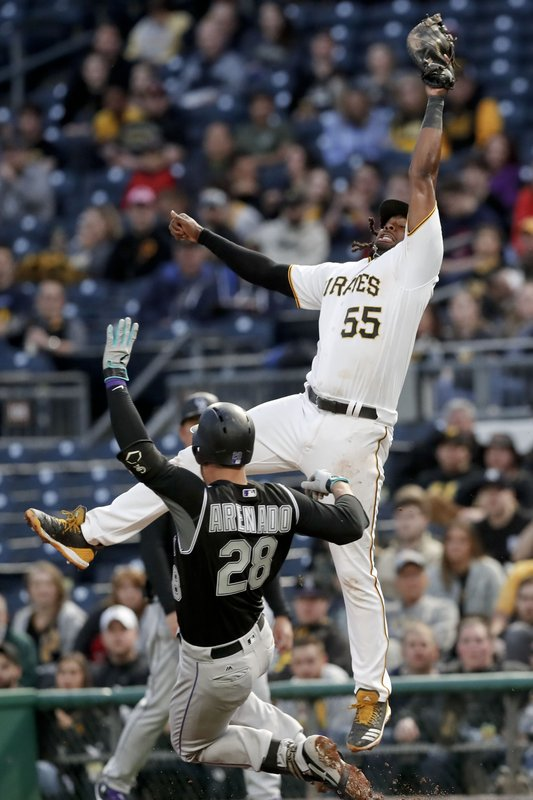 Pittsburgh Pirates first baseman Josh Bell leaps for the throw from shortstop Cole Tucker as Colorado Rockies' Nolan Arenado reaches first on an infield hit during the fifth inning of a baseball game Tuesday, May 21, 2019, in Pittsburgh. (AP Photo/Keith Srakocic)