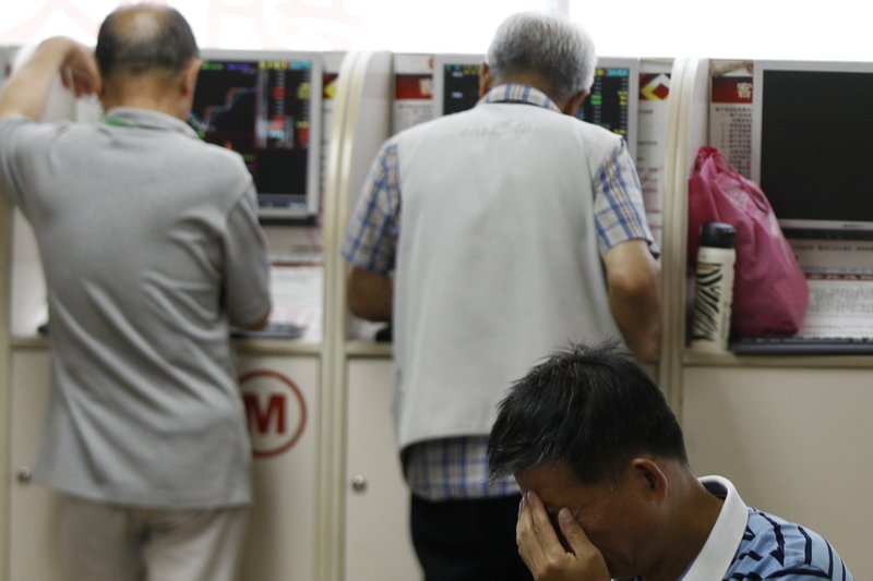 A man reacts as investor check their stock prices at a brokerage house in Beijing, Wednesday, May 22, 2019. Shares edged in Asia on Wednesday after a rebound in technology stocks helped power an overnight rally on Wall Street. (AP Photo/Andy Wong)