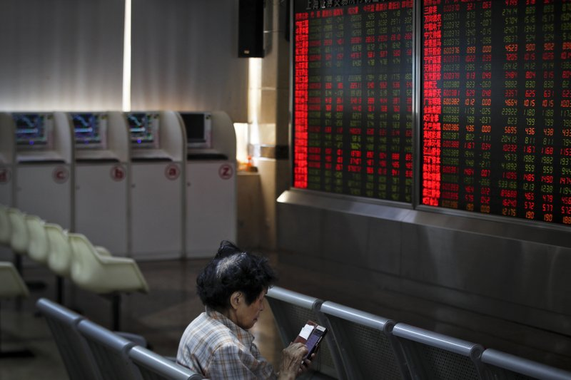 A woman checks stock prices through her smartphone at a brokerage house in Beijing, Wednesday, May 22, 2019. Shares edged in Asia on Wednesday after a rebound in technology stocks helped power an overnight rally on Wall Street. (AP Photo/Andy Wong)