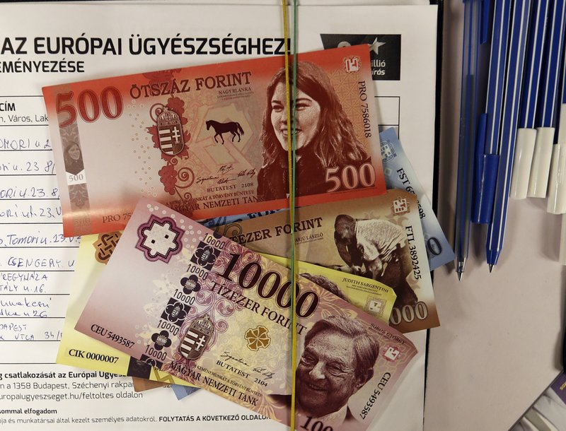 Fake Hungarian currency covers a signature form belonging to the Momentum party opposition campaign, in Budapest, Hungary, May 16, 2019, ahead of the European election on May 26. Given just five minutes to present their European Parliament election campaigns on Hungary's state media, opposition parties have been using their meager opportunities in novel and creative ways. The Momentum Party used its time on state TV to promote a campaign, which has received over 600,000 signatures, to pressure the government into joining the European Public Prosecutor's Office. (AP Photo/Laszlo Balogh)  meant to pressure the government to join the European Public Prosecutor's Office. The campaign seeks to gather 1 million signatures and has 600,000 so far.