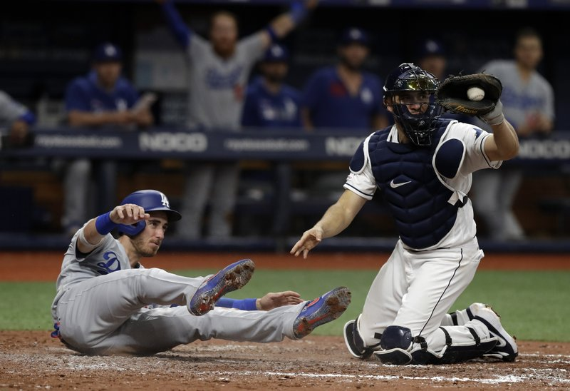 Tampa Bay Rays catcher Travis d'Arnaud, right, shows the ball to home plate umpire Bill Miller after tagging out Los Angeles Dodgers' Cody Bellinger during the sixth inning of a baseball game Wednesday, May 22, 2019, in St. Petersburg, Fla. (AP Photo/Chris O'Meara)