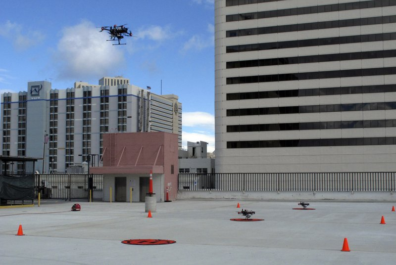 In this Tuesday, May 21, 2019 photo, a drone takes off from the roof of the Cal-Neva casino parking garage in downtown Reno, Nev. as part of a NASA simulation to test emerging technology that someday will be used to manage travel of hundreds of thousands of commercial, unmanned aerial vehicles (UAVs) delivering packages. It marked the first time such tests have been conducted in an urban setting. (AP Photo/Scott Sonner)
