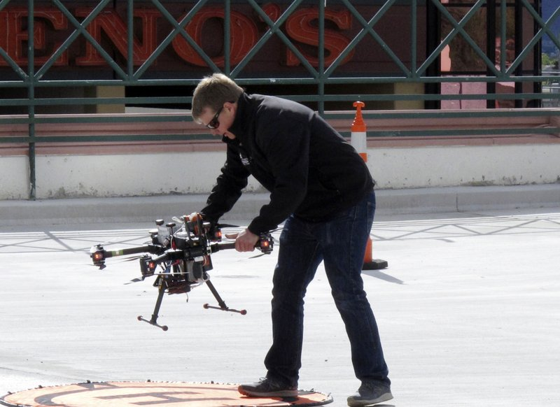 In this Tuesday, May 21, 2019 photo,  a researcher positions a drone for take off on the roof of a casino parking garage in downtown Reno, Nev., where NASA conducted the first drone tests of their kind in an urban setting. A series of simulations are testing the emerging technology that someday will be used to manage travel of hundreds of thousands of commercial, unmanned aerial vehicles (UAVs) delivering packages. (AP Photo/Scott Sonner)