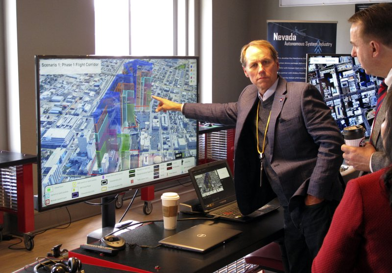 In this Tuesday, May 21, 2019 photo, Ron Johnson, NASA's project manager for Unmanned Aircraft Systems Traffic Management, points to an image detailing airspace elevations in downtown Reno. Nev., where NASA conducted the first drone tests of their kind in an urban setting. A series of simulations are testing the emerging technology that someday will be used to manage travel of hundreds of thousands of commercial, unmanned aerial vehicles (UAVs) delivering packages.  (AP Photo/Scott Sonner)