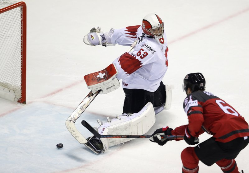 Canada's Mark Stone, right, scores his side's third goal past Switzerland's goalkeeper Leonardo Genoni during the Ice Hockey World Championships quarterfinal match between Canada and Switzerland at the Steel Arena in Kosice, Slovakia, Thursday, May 23, 2019. (AP Photo/Petr David Josek)
