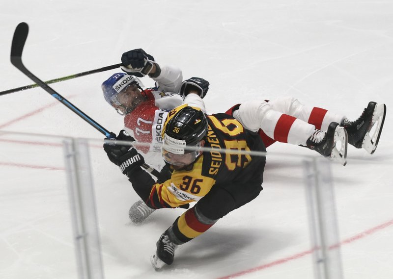 Czech Republic's Milan Gulas falls after challenging for the puck with Germany's Yannic Seidenberg during the Ice Hockey World Championships quarterfinal match between Germany and the Czech Republic at the Steel Arena in Bratislava, Slovakia, Thursday, May 23, 2019. (AP Photo/Ronald Zak)