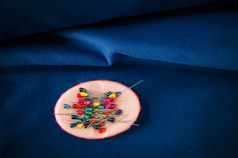 In this picture taken Tuesday, May 21, 2019, needles sit on a piece of fabric at a tailor shop that produces traditional clothing in Luncavita, Romania. Valentina Radu worked in Italy, but when her husband lost his job there, they struggled to pay the rent and decided to come home where they used European Union funds to buy a small farm and she opened a tailor's shop.  (AP Photo/Vadim Ghirda)