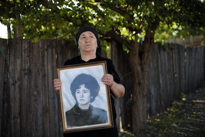 "In this picture taken Wednesday, May 22, 2019, Marioara Banea, a 63-year-old local retiree poses with a 1974 portrait of herself, in Luncavita, Romania. The Romania village of Luncavita has benefited greatly from millions in development funds from the European Union, but few of its residents bothered to vote in previous European Parliamentary elections. ""The EU changed my life,"" Banea said. ""Now we have water. We used to queue at the well for hours ... and we have indoor plumbing too!"" (AP Photo/Vadim Ghirda)"