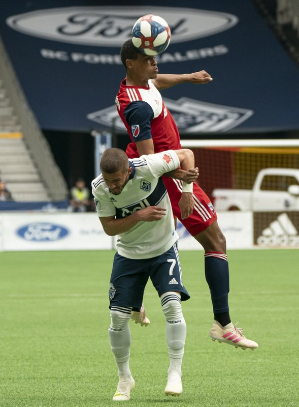 FC Dallas' Reggie Cannon wins a header while going up against Vancouver Whitecaps' Lucas Venuto during the first half of an MLS soccer match Saturday, May 25, 2019, in Vancouver, British Columbia. (Richard Lam/The Canadian Press via AP)