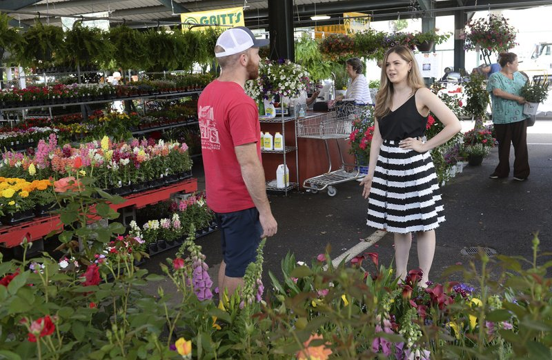 In a Friday, May 10, 2019 photo, Capitol Market Executive Director Nichole Greene talks with Brad Gritt of Gritt's Farm at the Capitol Market in Charleston, W.V. (Chris Dorst/Charleston Gazette-Mail via AP)