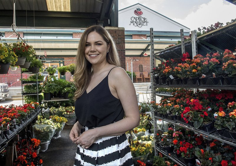 In a Friday, May 10, 2019 photo, Capitol Market Executive Director Nichole Greene stands among flowering plants at the Capitol Market in Charleston W.V. Since joining the Capitol Market team in April, 2018, she has climbed from executive assistant, to communications director, to executive director. (Chris Dorst/Charleston Gazette-Mail via AP)