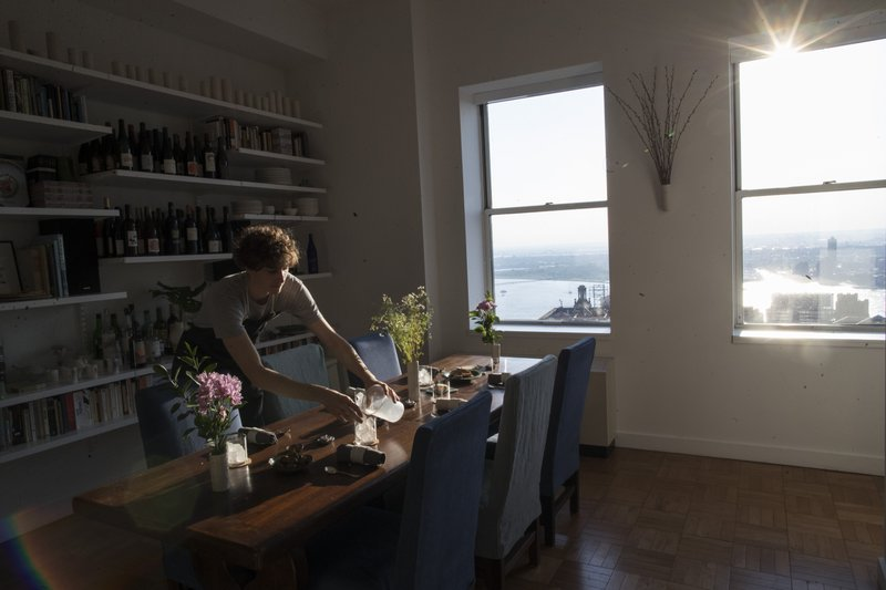 In this May 17, 2019 photo, Jonah Reider sets the table before dinner guests arrive in New York. His apartment has a view of New York Harbor and the Statue of Liberty. (AP Photo/Mary Altaffer)
